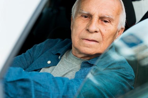 Vista frontal del anciano en auto personal