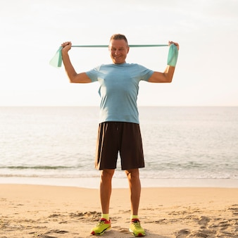 Vista frontal del anciano sonriente trabajando con cuerda elástica en la playa