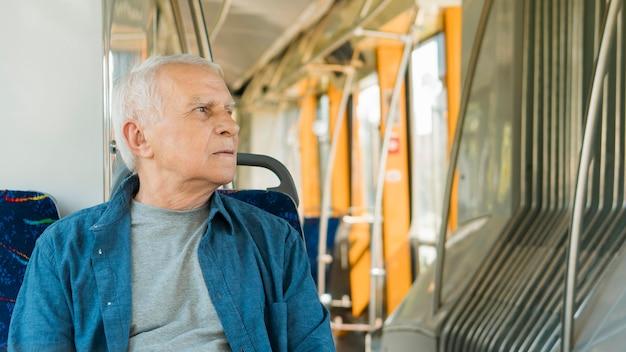 Vista frontal del anciano en transporte público
