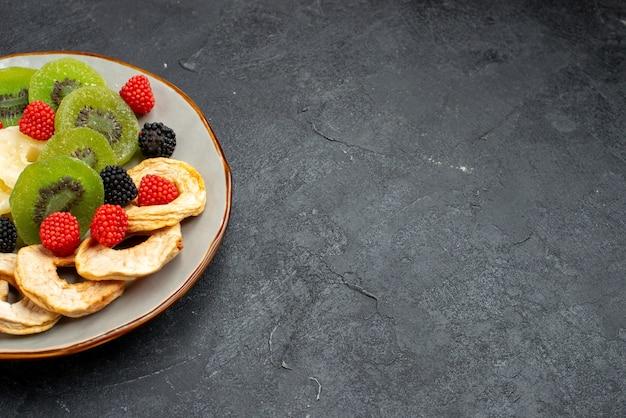 Vista frontal de los anillos de piña seca con kiwis secos y manzanas en la superficie de color gris oscuro caramelo de azúcar dulce seco de fruta
