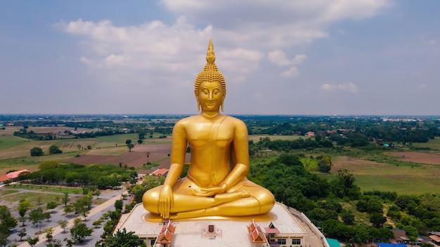 Vista frontal de la antena del gran buda antiguo mediado por oro en el templo wat muang, provincia de ang thong, tailandia, vista superior de ángulo alto de drone
