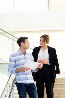 Una vista frontal apuesto joven en camisa a rayas hablando y discutiendo temas de trabajo con la joven empresaria durante la construcción de actividades de trabajo durante el día