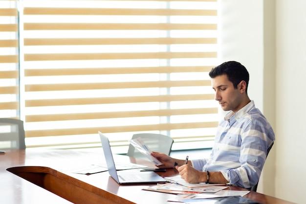 Una vista frontal apuesto joven en camisa a rayas trabajando dentro de la sala de conferencias utilizando su computadora portátil plateada mirando a través de documentos durante la actividad de trabajo durante el día
