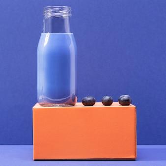 Vista frontal de arándanos y batido en botella de vidrio