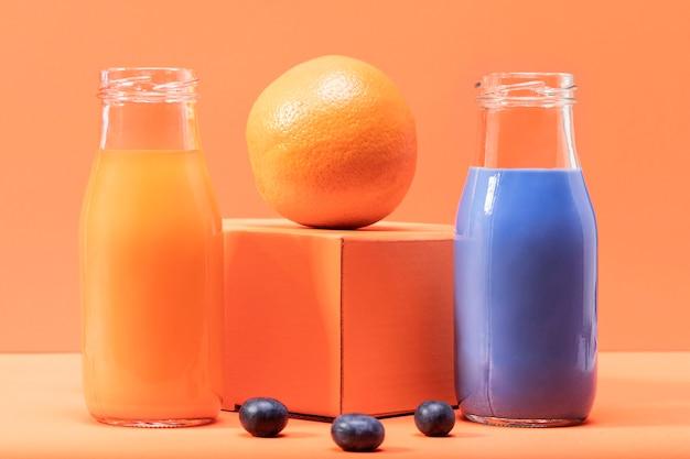 Vista frontal de arándanos y naranja con batidos