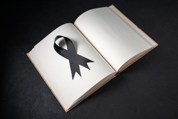 Vista frontal del arco negro dentro de un libro abierto sobre una superficie oscura