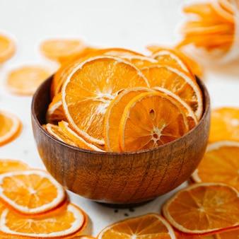 Una vista frontal de aros de naranja seca dulces dentro y fuera de la placa pequeña en el escritorio blanco fruta seca color pasas