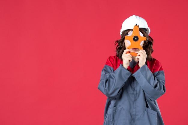 Vista frontal de la arquitecta en uniforme con casco sosteniendo cinta métrica frente a su cara en la pared roja aislada