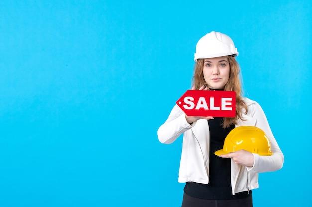 Vista frontal arquitecto mujer sosteniendo venta escribiendo en azul