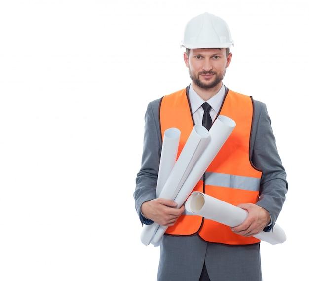 Vista frontal del arquitecto con sombrero de seguridad blanco y chaleco naranja con muchos planes de dibujo en papel.