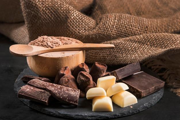 Vista frontal arreglo de chocolate dulce en tablero oscuro