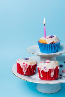 Vista frontal arreglo de cupcakes de cumpleaños sobre fondo azul.