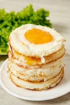 Vista frontal arreglo de huevos fritos sobre fondo liso