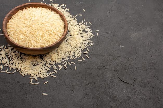 Vista frontal del arroz crudo dentro de la placa en el espacio gris