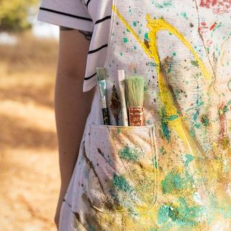 Vista frontal de la artista femenina con delantal lleno de pintura y pinceles