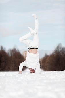 Vista frontal del artista masculino de hip hop de pie sobre la cabeza en la nieve.