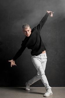 Vista frontal del artista masculino en jeans y zapatillas de deporte bailando