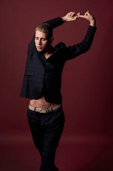 Vista frontal del artista masculino en traje posando con los brazos arriba