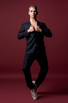 Vista frontal del artista masculino en traje y zapatillas posando mientras dobla las piernas