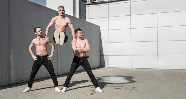 Vista frontal de artistas de hip hop sin camisa posando