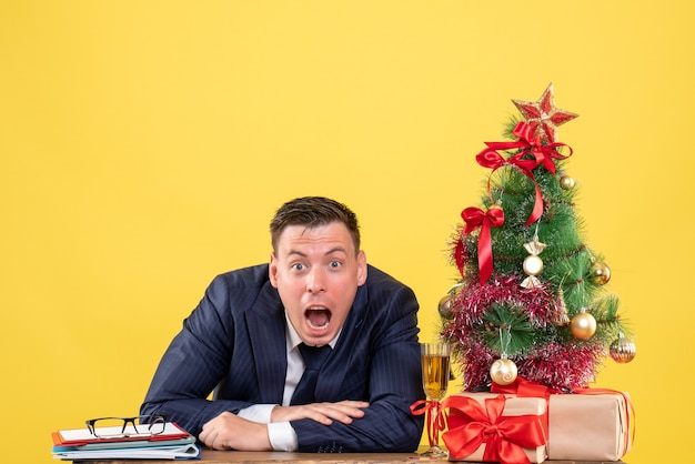 Vista frontal asombrado hombre abriendo la boca sentado en la mesa cerca del árbol de navidad y presenta sobre fondo amarillo