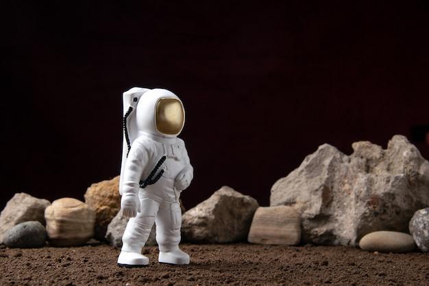 Vista frontal del astronauta blanco con rocas en la luna de ciencia ficción cósmica