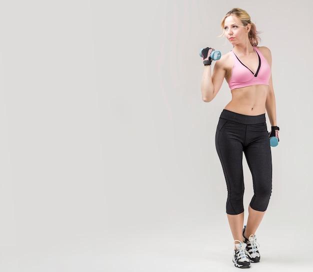 Vista frontal del atletismo en atuendo de gimnasio haciendo ejercicio con pesas
