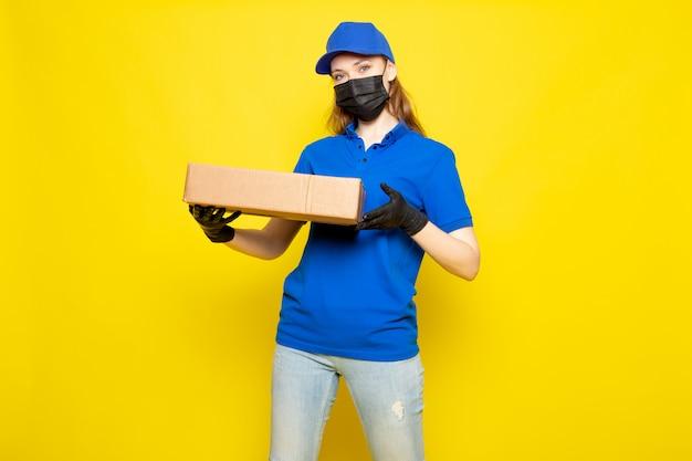 Una vista frontal atractiva mujer mensajero en polo azul gorra azul y jeans con paquete en guantes negros máscara protectora negra sobre el fondo amarillo trabajo de servicio de alimentos