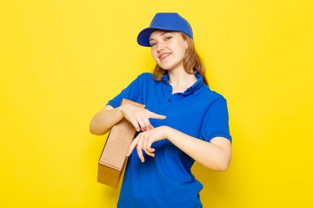 Una vista frontal atractiva mujer mensajero en polo azul gorra azul y jeans sosteniendo paquete tocando su muñeca sonriendo en el trabajo de servicio de alimentos de fondo amarillo