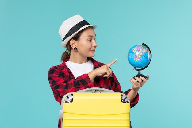 Vista frontal atractiva mujer sosteniendo el globo y preparándose para el viaje en el espacio azul