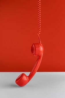 Vista frontal del auricular del teléfono colgando del cable