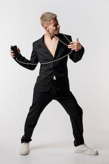 Vista frontal del bailarín en traje escuchando música con auriculares