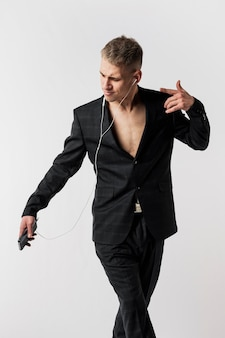 Vista frontal del bailarín en traje posando mientras escucha música en los auriculares