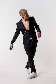 Vista frontal del bailarín en traje y zapatillas escuchando música con auriculares