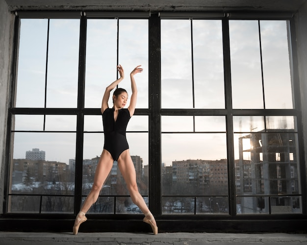 Vista frontal de la bailarina bailando en leotardo
