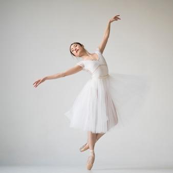Vista frontal de la bailarina bailando en traje de tutú