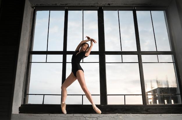 Vista frontal de la bailarina en leotardo bailando