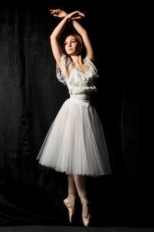 Vista frontal de la bailarina posando en zapatillas de punta y vestido de tutú