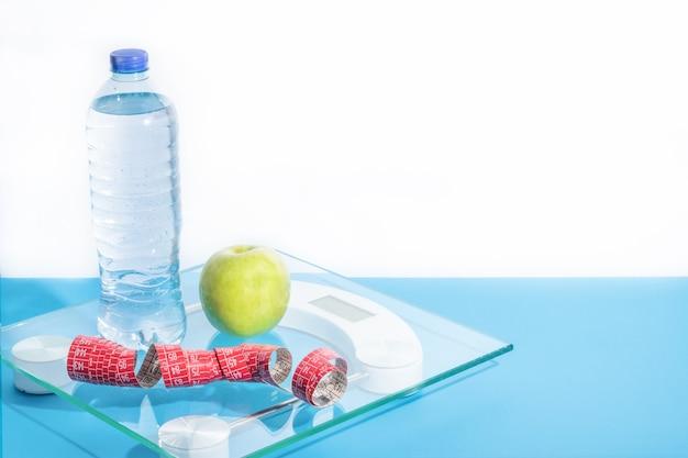 Vista frontal de la balanza sobre la mesa de madera y fondo azul.