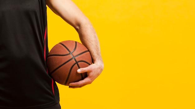 Vista frontal del baloncesto sostenido cerca de la cadera por el jugador masculino con espacio de copia