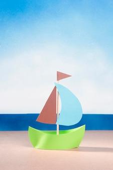 Vista frontal del barco de papel en la arena de la playa