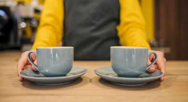 Vista frontal del barista con dos tazas de café.