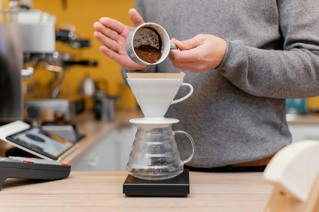 Vista frontal del barista macho vertiendo café de la taza en el filtro
