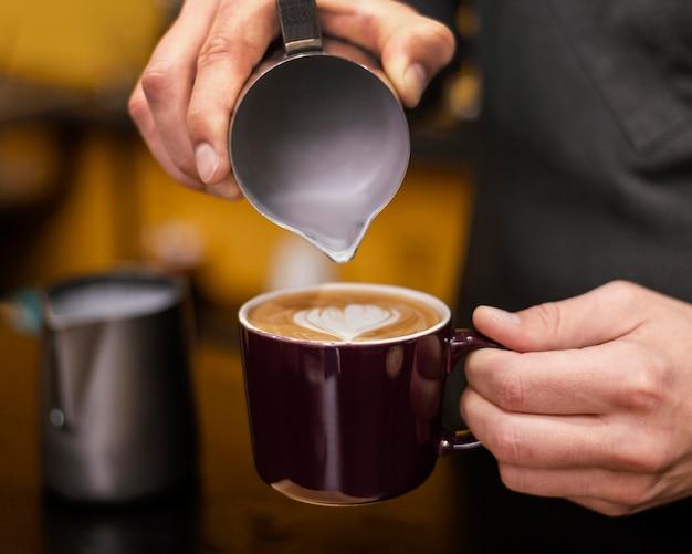 Vista frontal del barista macho vertiendo café en taza
