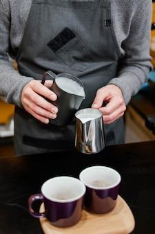 Vista frontal del barista macho vertiendo espuma de leche en tazas