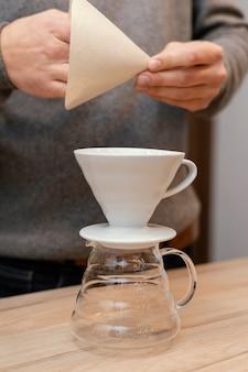 Vista frontal del barista masculino con filtro de café