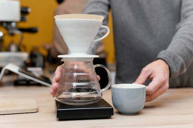 Vista frontal del barista masculino sosteniendo la taza de café y el filtro