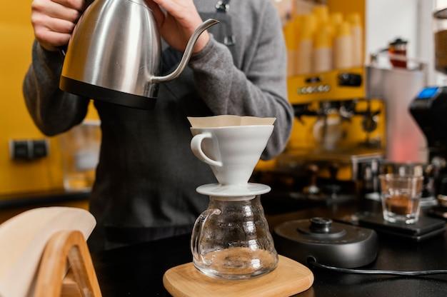 Vista frontal del barista masculino vertiendo agua hirviendo en el filtro de café