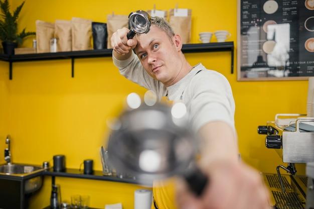 Vista frontal del barista posando mientras sostiene la taza