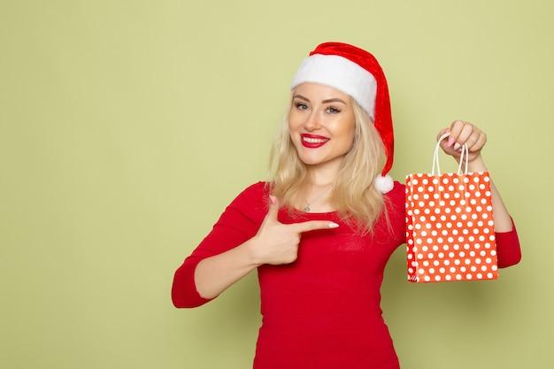 Vista frontal bastante hembra sosteniendo presente en pequeño paquete en la pared verde vacaciones navidad nieve color año nuevo emoción